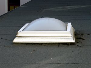 Skylight with a with frame on an asphalt shingle roof with black flashing