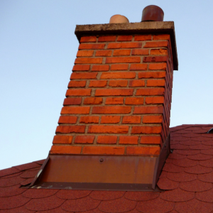 Red brick chimney with metal flashing installed where the chimney protrudes from the roof